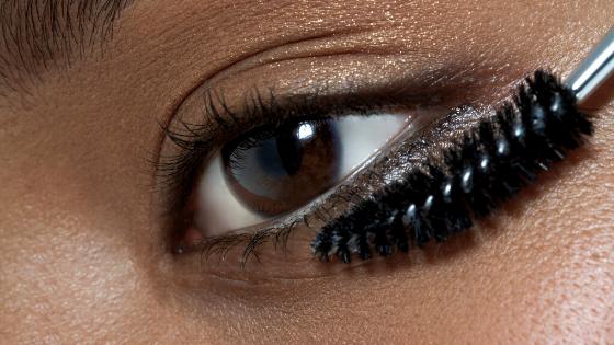 Imagem está focado apenas em um dos olhos de uma mulher que está segurando um aplicador de rímel próximo aos cílios.