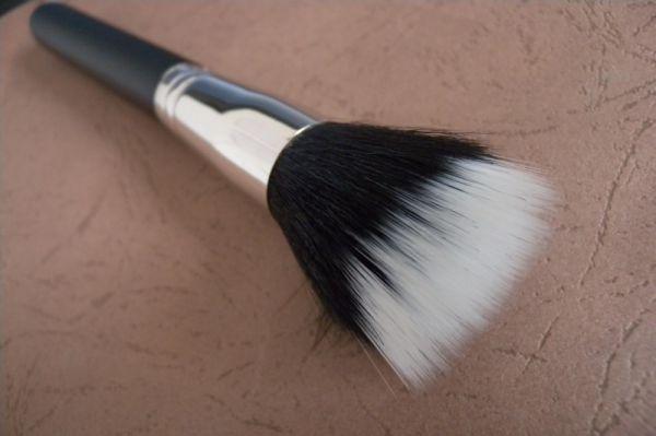 Um pincel com a raiz das cerdas pretas e as pontas brancas. O pincel está deitado sobre uma mesa marrom.