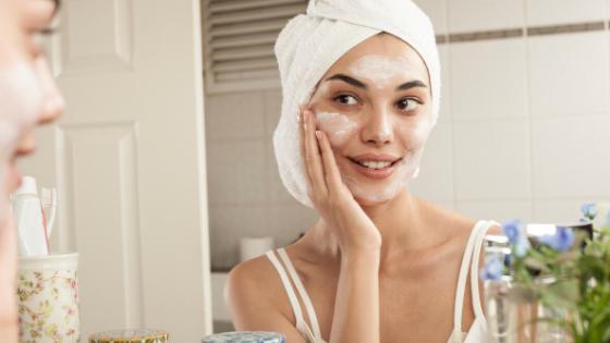 Uma mulher olhando para o espelho, usando uma toalha na cabeça e aplicando um produto facial de cor esbranquiçada.