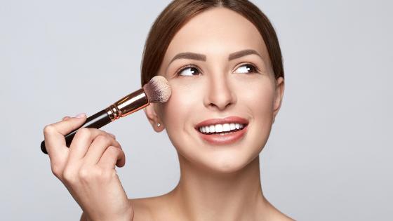Mulher utilizando um pincel de maquiagem próximo a bochecha. Ela está sorrindo e com o olhar erguido para a sua direita.