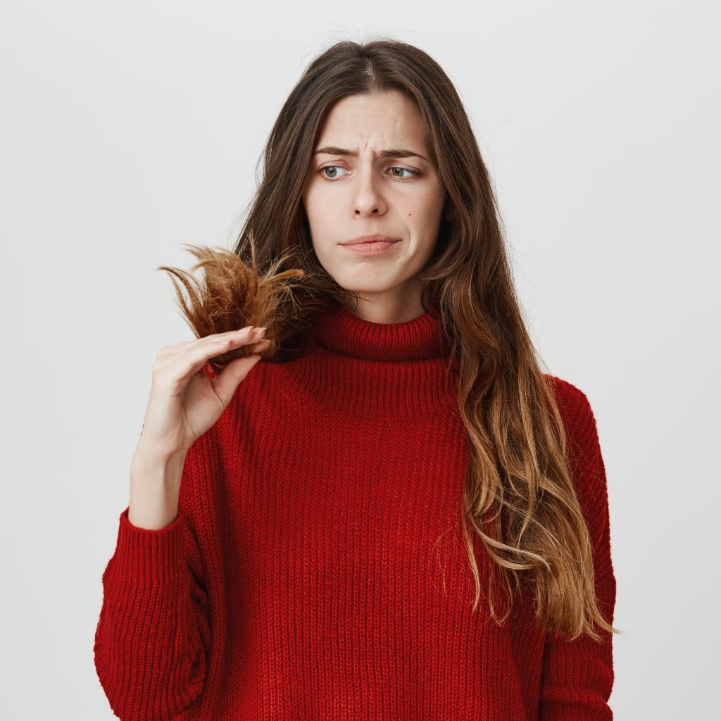 Mulher olhando para o próprio cabelo e pensando se precisa fazer uma reconstrução capilar.