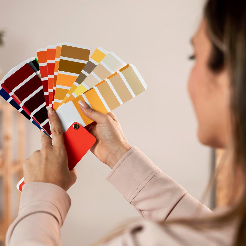 Imagem com uma mulher segurando varias cartelas de cores que representam o estudo de coloração pessoal.