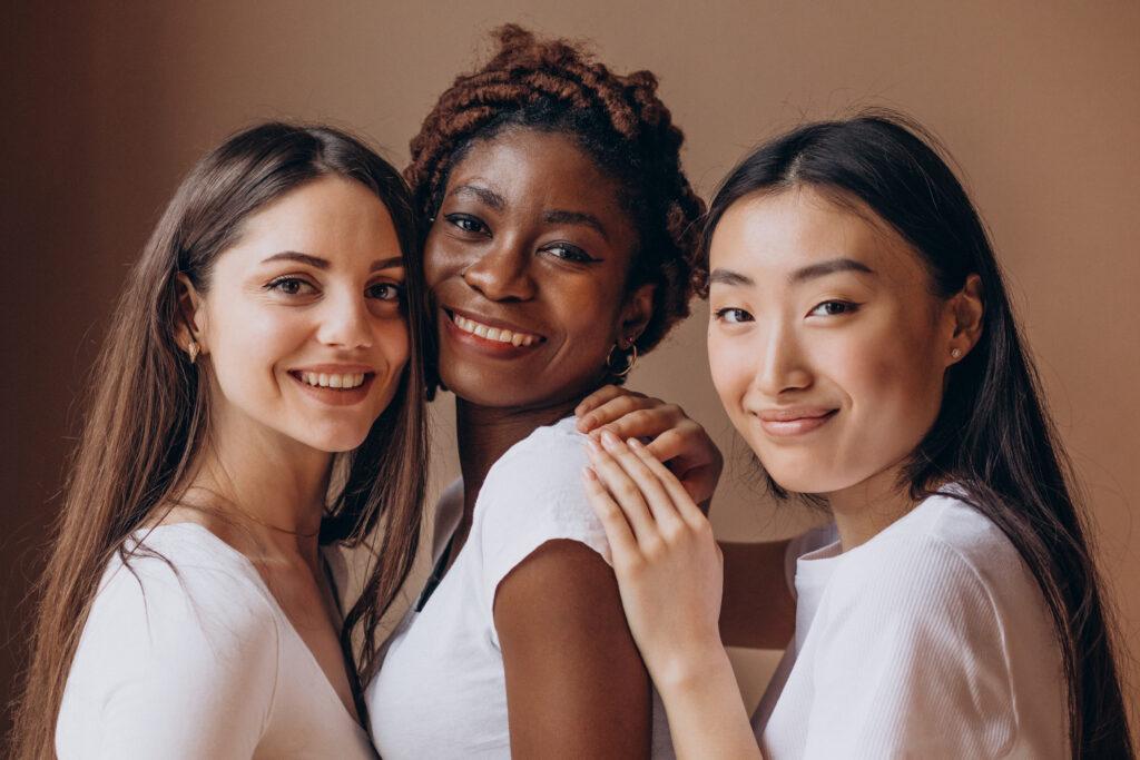 Imagem com três mulheres, da esquerda para a direita: uma mulher branca, uma mulher negra e uma mulher asiática